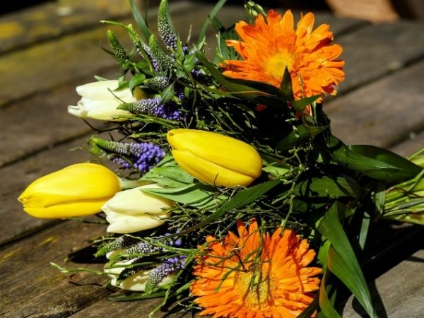 flower bouquet wth yellow and white tulips orange dahlias and wildflowers seasonal floral arrangement